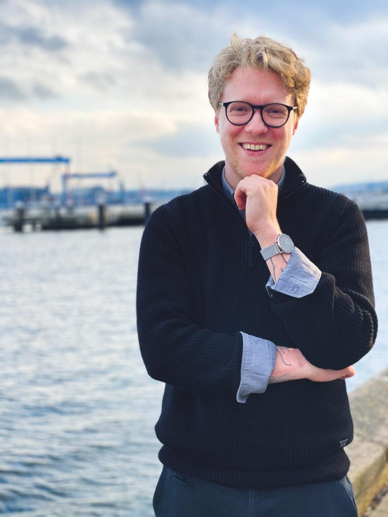 Lasse Petersdotter lächelt in die Kamera an der Kieler Förde